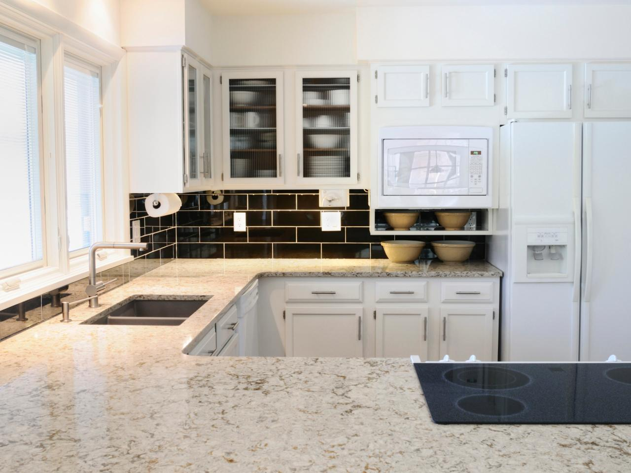 white kitchen with marble countertop and decent sink