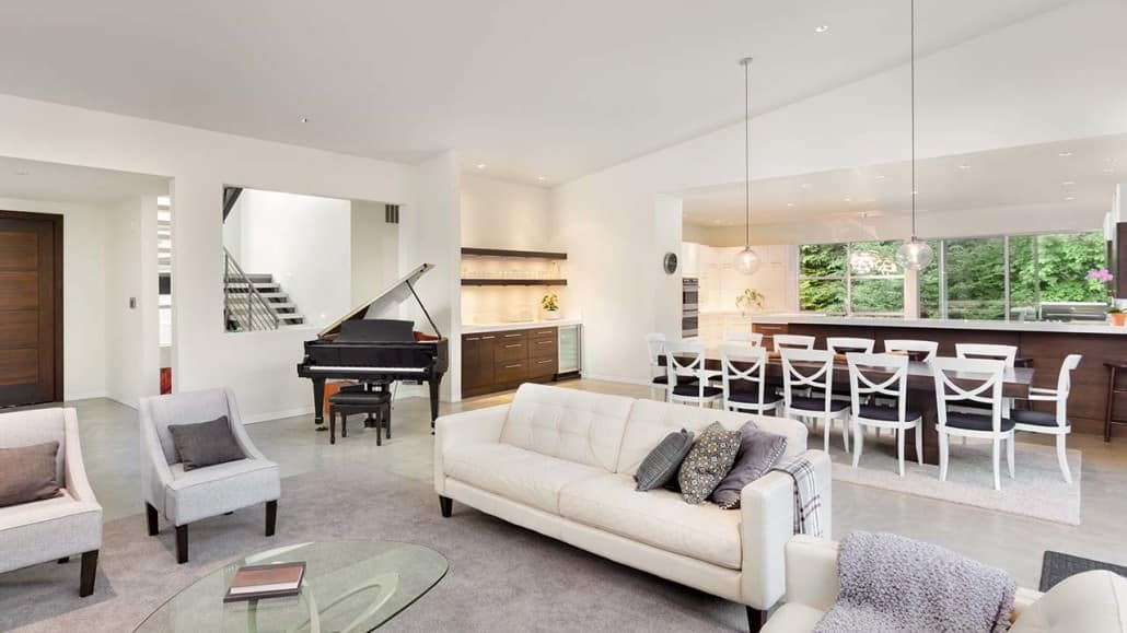 beautiful living room in new luxury home with view of dining room table and open plan kitchen